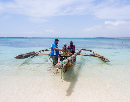 Two fishermen in modern outfits on a traditional wooden boat on the beach of Mbudya Island, Tanzania, Africa on a sunny day. Landscape orientation, wide angle