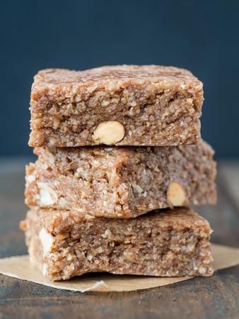 cashew nuts: Homemade organic healthy chewy muesli granola power bars with wholemeal oats, cashew butter, honey and nuts, cut into bite size, arranged in a pile on a wooden table. Vertical orientation, close up.