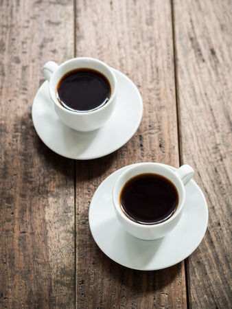 rooibos: Vertical photo of two white cups of rooibos red espresso from South Africa on o rustic wooden table. Elevated view. Stock Photo