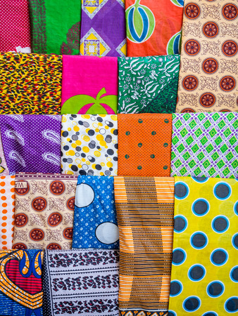 Colorful African garments called kanga and kitenge traditionally worn by women in East Africa, sold on a local market in Stone Town, Zanzibar, Tanzania.