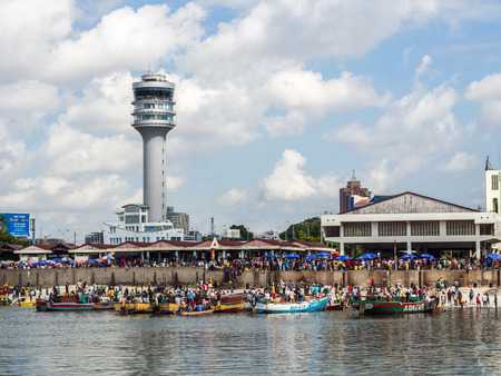 Horizontal photo of the waterfront of Dar es Salaam, Tanzania in East Africa, with maritime control tower and the fish market. Local people on boats in front.