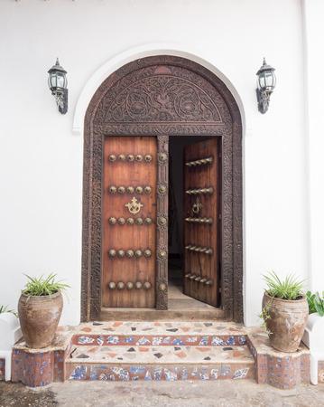 door: Vertical photo of old traditional wooden carved door in Stone Town, Zanzibar, Tanzania, East Africa.