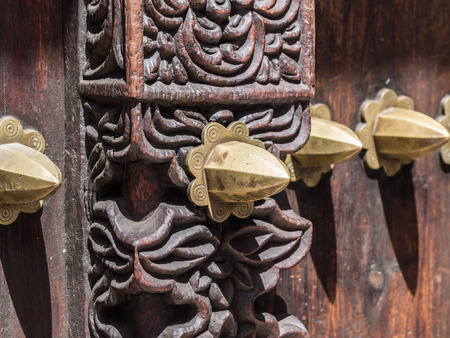 Horizontal close up photo of an old traditional wooden carved door in Stone Town, Zanzibar, Tanzania, East Africa, with typical metal elements and carved floral ornaments.