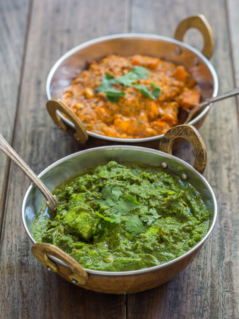 paneer: Indian cuisine: palak paneer and paneer tikka masala in traditional copper bowls with ornamented handles placed on a dark rustic wooden table. Vertical orientation, elevated view. Stock Photo