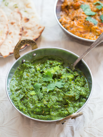 close up food: Indian cuisine: palak paneer and paneer tikka masala served in traditional copper bowls with ornamented handles placed on a clear table cloth. Close up vertical orientation spoon on the side