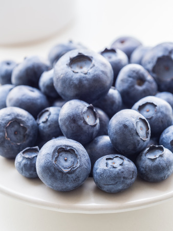 small plate: Bilberries whortleberries on a small plate, close up. Stock Photo