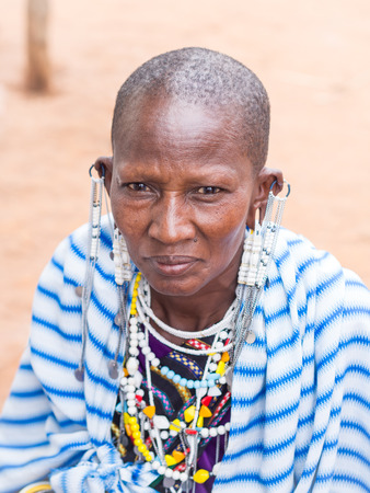 stretched: Maasai woman wearing earrings in stretched earlobes and traditional necklaces on a local market.