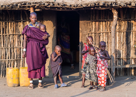 Maasai family in front of a traditional house in their boma village in Tanzania, Africa.