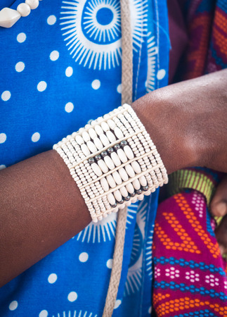 vetical: Withe beads bracelet worn by a young Maasai woman in Tanzania, Africa. Close up, vetical orientation.