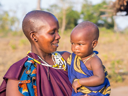 HANDENI, TANZANIA - AUGUST 01, 2015: Maasai mother holding her child in her arms in their boma (village) in Tanzania, Africa. Redakční