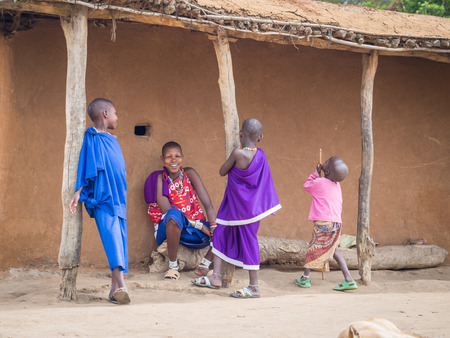 aboriginal woman: HANDENI, TANZANIA - AUGUST 01, 2015: Maasai young woman and three children in front of a house in their boma in Tanzania, Africa, on a normal day. Editorial