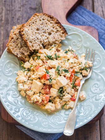 scramble: Vegan tofu scramble with tomato and green herbs served with wholegrain homemade bread. Wooden background.