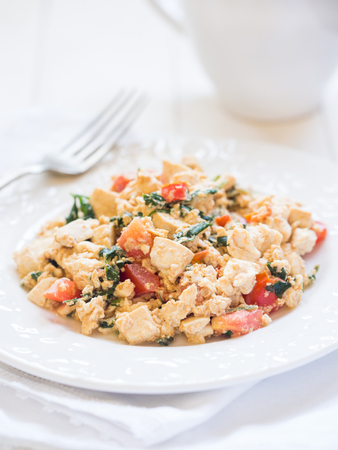 scramble: Vegan tofu scramble with tomato and green herbs. White background, vertical orientation, close up.