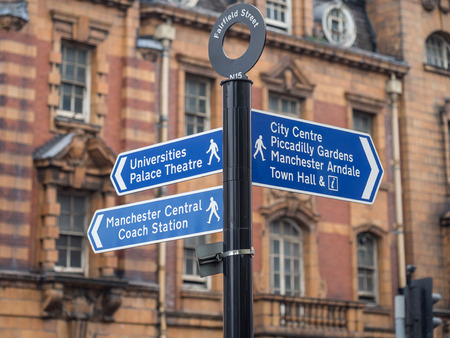 street sign: Street sign on Fairfield street indicating City Center, Piccadilly Gardens and Universities Palace Theatre. Typical architecture in the background.