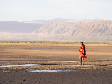 Maasai warrior wearing traditional red clothes in the dried part of Lake Natron in the North of Tanzania, Africa. Redakční