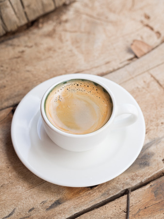 vertical orientation: Double espresso in a white cup placed over a dhow wood table. Elevated view, vertical orientation.