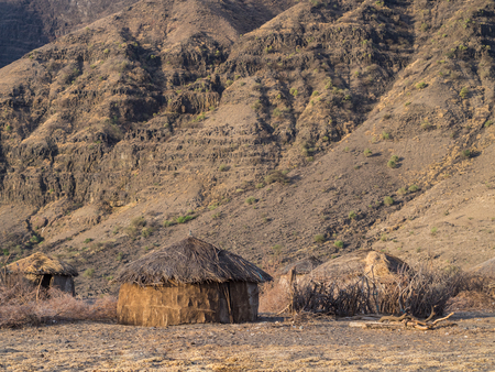 traditonal: Traditonal round house in a Maasai village in front of the Ol Doinyo Lengai in Arusha Region in Tanzania, Africa, at sunrise.