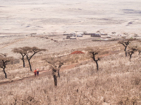 traditonal: NGORONGORO, TANZANIA - OCTOBER 14, 2015: Landscape in Ngorongro Region in the North of Tanzania, Africa, with a traditonal Maasai village in the background. Two Maasais on the road.