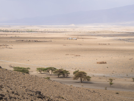 settlements: Landscape next to Lake Natron in Arusha Region, Tanzania, Africa. Maasai settlements in the valley. Pastel colors, horizontal orientation.