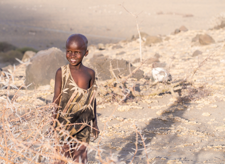 foreigners: Happy Maasai boy close to Lake Natron and Ol Doinyo Lengai Mountain of God in the Maasai language smiling at foreigners. Editorial