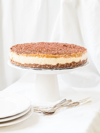 cleat: Whole vegan millet cheesecake with date caramel on a cleat background.
