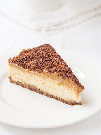 cleat: Slice of vegan millet cheesecake with date caramel on a cleat background.
