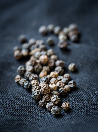 piper: Black pepper (Piper nigrum) on black background, close up.