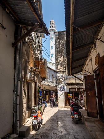 vertical orientation: One of the narrow streets in the old part of Stone Town, Zanzibar in East Africa. Vertical orientation, wide angle. Mosques minaret in the background.