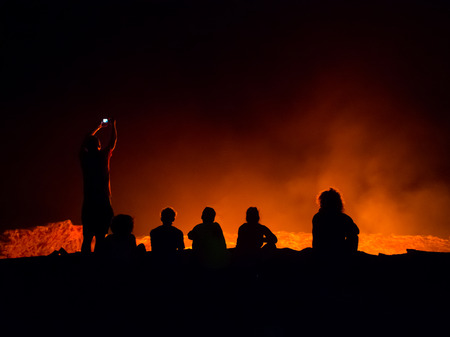 badland: ERTA ALE, ETHIOPIA - JUNE 28, 2016: Tourists sitting at the edge of Erta Ale active volcano in Afar Region in Ethiopia, Africa, at night. Editorial