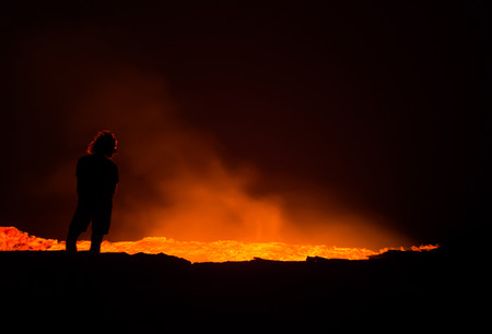 ERTA ALE, ETHIOPIA - JUNE 28, 2016: Person standing at the edge of Erta Ale active volcano in Afar Region in Ethiopia, Africa, at night.