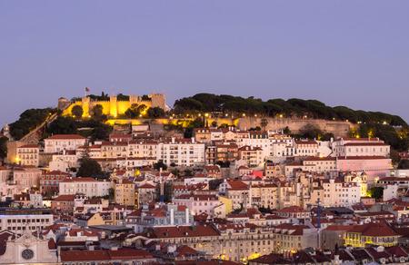 Cityscape of Lisbon, Portugal, with the Sao Jorge Castle seen from Miradouro Sao Pedro de Alcantara at night. Editorial