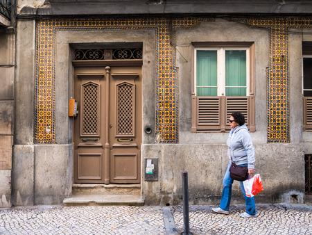 bairro: Person passing next to an old building in Bairro Alto, Lisbon, Portugal.