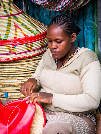 basketry: ADDIS ABEBA, ETHIOPIA - JUNE 06, 2016: Ethiopian woman makes Habesha baskets for sale on a local market in Addis Abeba.