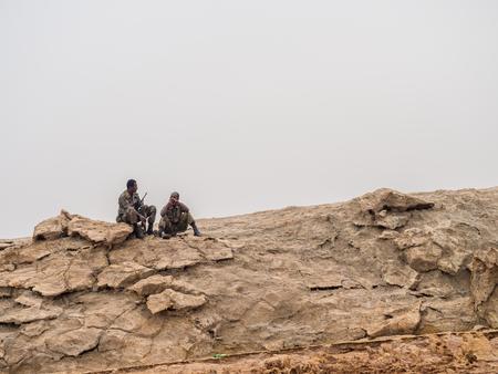 DANAKIL DEPRESSION, ETHIOPIA - JUNE 29, 2016: Solders looking after tourists around sulphur lake Dallol in Danakil Depression, Ethiopia. Editorial