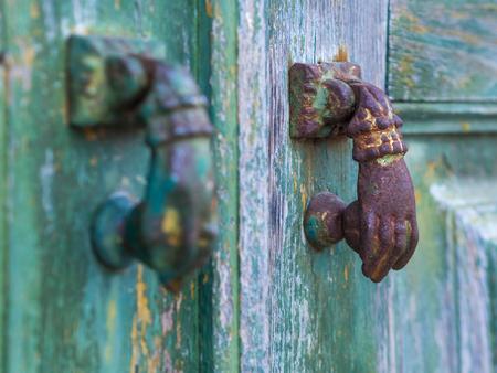Old hand shaped metal door handles in Obidos, Portugal.