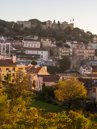 Soa Jorge Castle in Lisbon, Portugal, with the sourrounding architecture, at sunset.