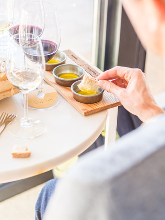 Young man tasting olive oils during wine and olive oil tasting in Alentejo region, Portugal.