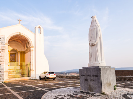 ESTREMOZ, PORTUGAL – AUGUST 23, 2018: Nosso Senhor dos Inocentes church with  Statue of Rainha Santa Isabel in front of it in Estremoz, Portugal.