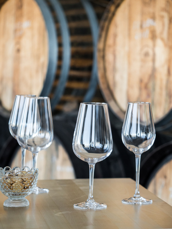 Empty wine glasses in front of wooden wine barrels. Stok Fotoğraf
