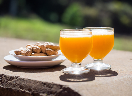 Poncha, a traditional alcoholic drink from the island of Madeira, Portugal, made with aguardente de cana and fresh passion fruit. Served along with peanuts.