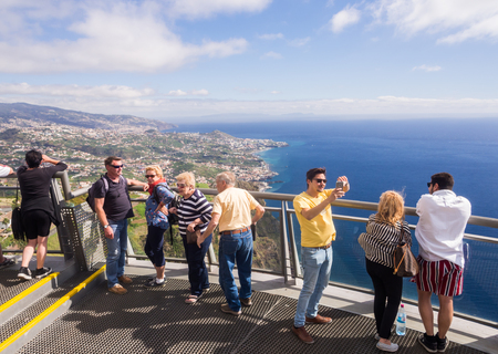 Madeira, Portugal - November 02, 2018: Tourists at Cabo Girao Skywalk viewpoint. Funchal, the capital of Madeira, Portugal, in the background.