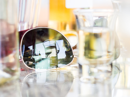 Reflection of an alcoholic drink in sunglasses. Imagens