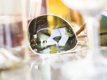 Reflection of two wineglasses in sunglasses placed on a table in a winery garden in Portugal.