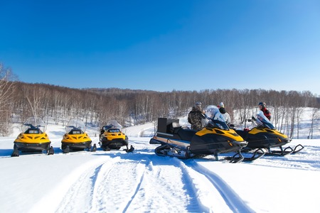 people driving  snowmobile in winter mountain and forest