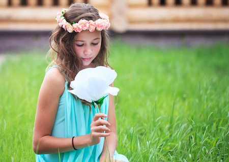 big flower: Young beautiful girl with flowing hair holding a big flower. Stock Photo