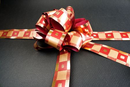 A red ribon tied in a bow over a black background. photo