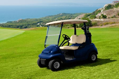 Green lawn for golf playing. Small golf car waiting for golfers photo