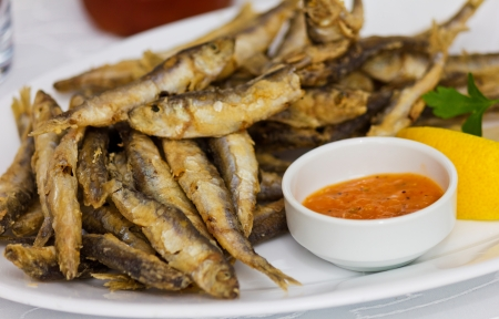 sprat: Fried fresh sprat fish with souce. Good seafood.;