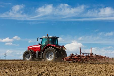 arando: Granjero que ara el campo de cultivo tractor en el campo tractor rojo con un arado en un campo agrícola Tractor and Plow
