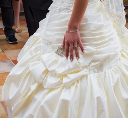 Wedding day  Hand of bride with a wedding ring on her dress Stock Photo